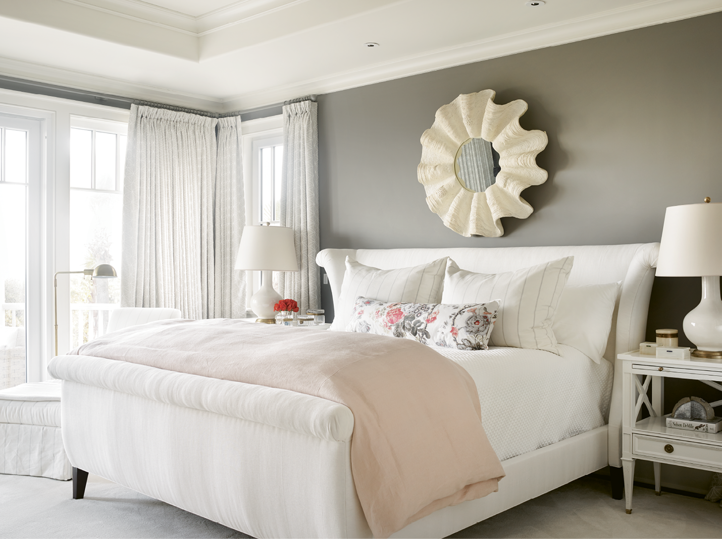 "In the master bedroom, walls covered in Farrow and Ball's ""Mole's Breath"" and drapes made with light grey Shumacher fabric ground the room's blush accents. The lamps are from Circa Lighting."
