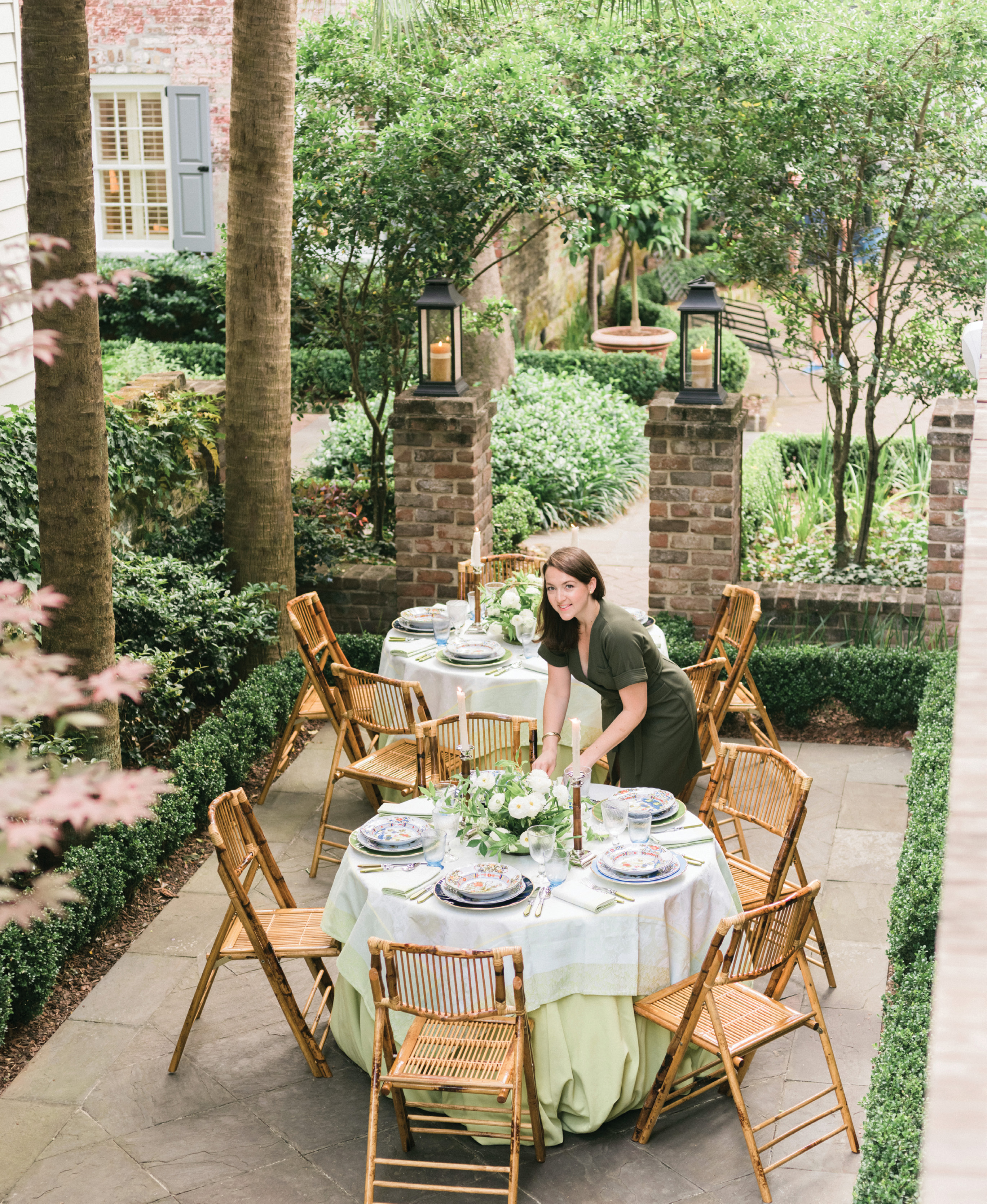 "Augusta Cole, Lynn's right hand at Easton Events, puts the finishing touches on the tables. ""I chose two rounds to break up the long, narrow space,"" Lynn explains. ""I love creating intimate dinners, and nothing does that better than a 48-inch table."""