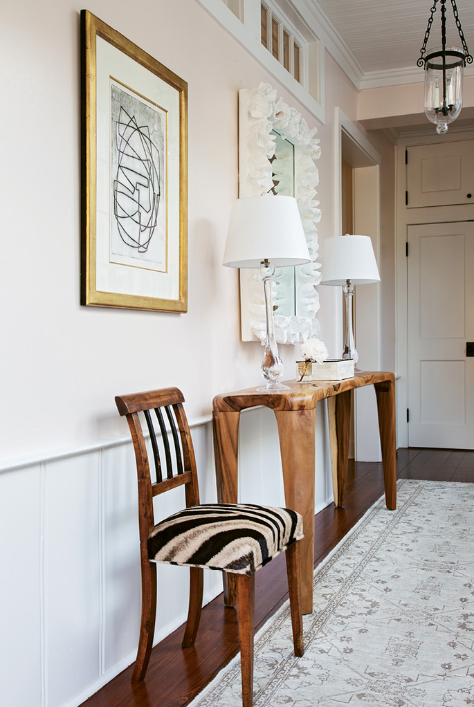 AN ELEGANT WELCOME: In the foyer, a vintage Biedermeier chair covered in Forsyth hide and an acacia wood console exude warmth, while a work by Otto Neumann in a gilt frame adds sophistication.