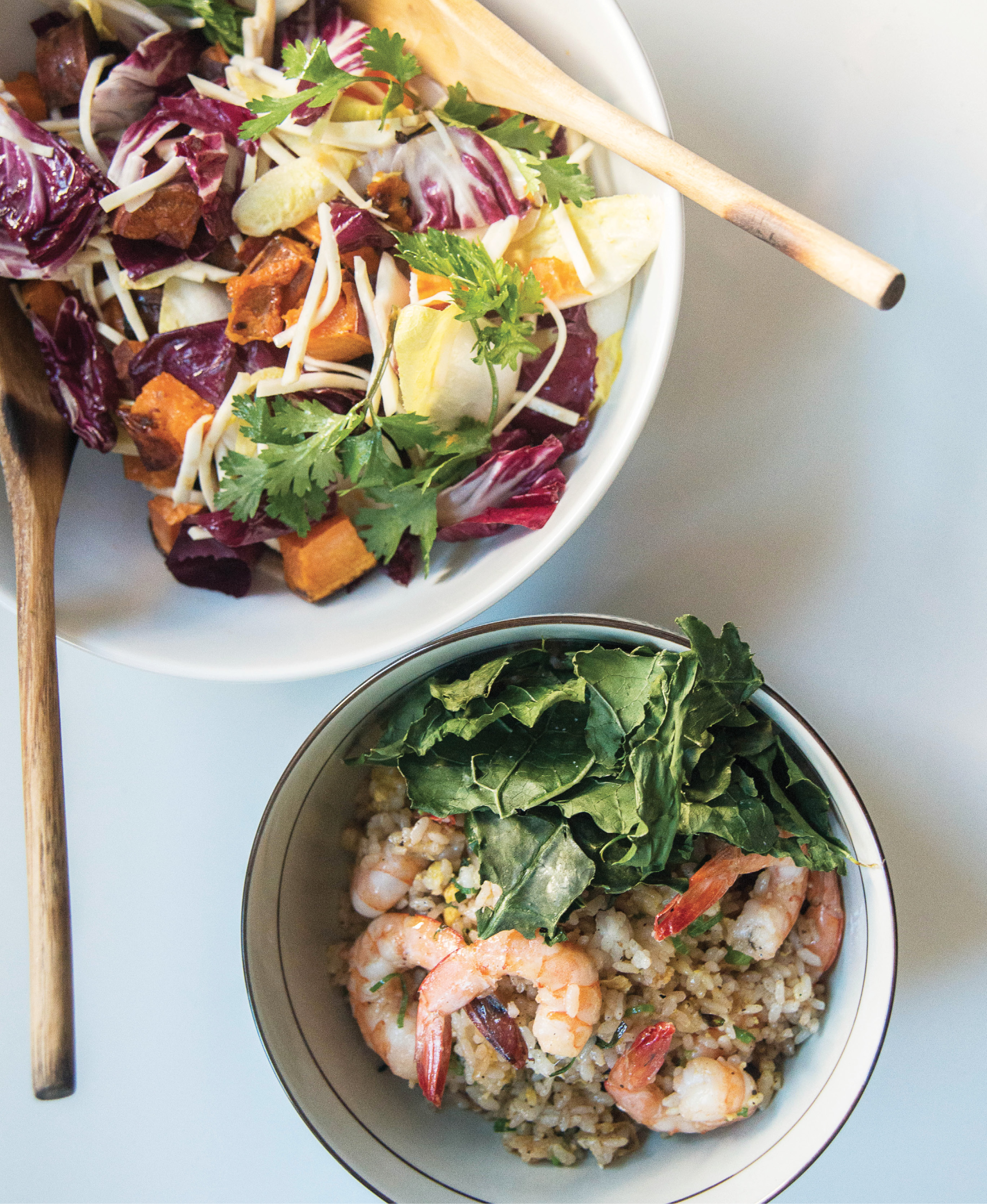 Bowls of the celery root and sweet potato salad and shrimp fried rice; Walker and Li top the rice with crispy baked kale, a healthier alternative to deep- fried garnishes.