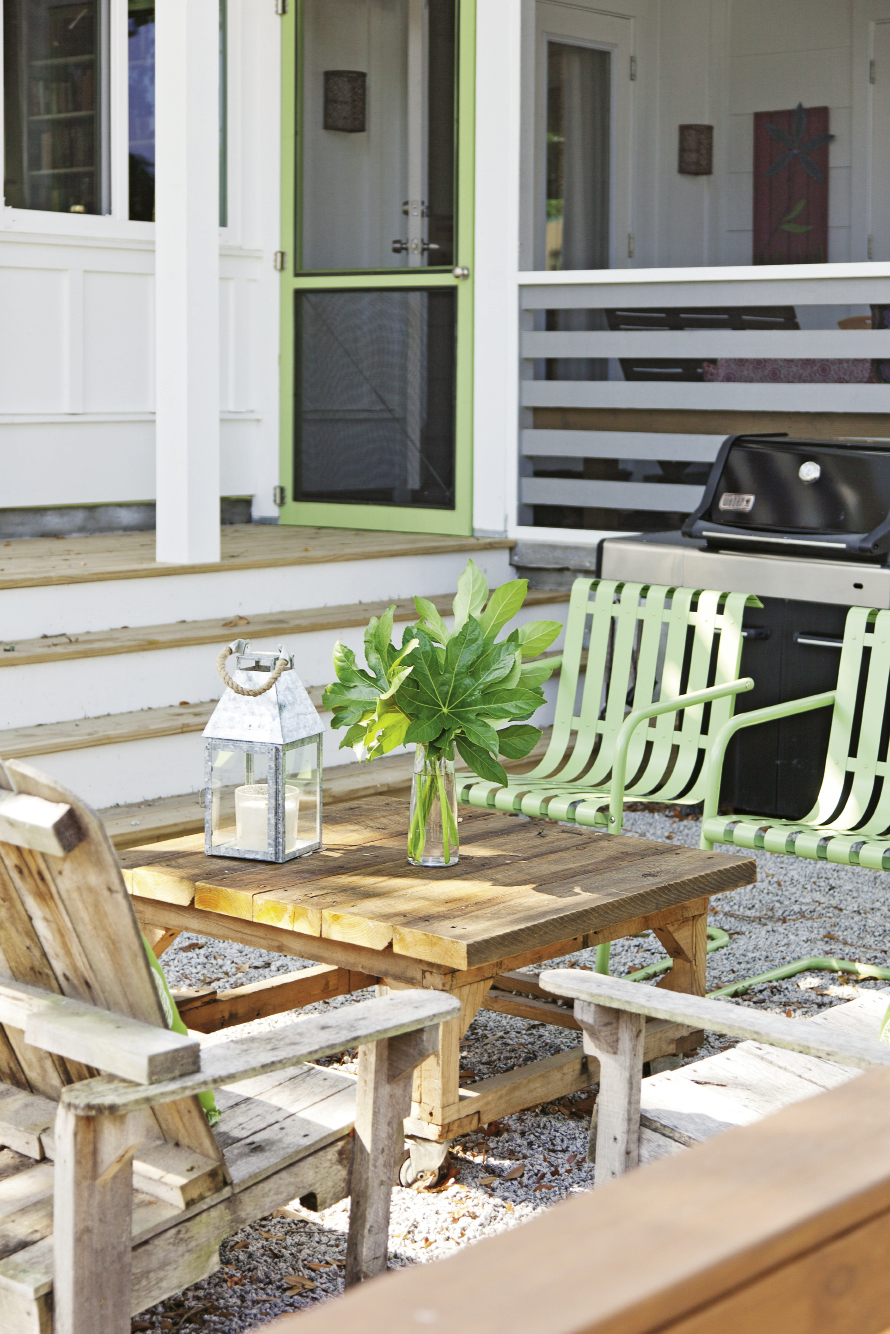 Cheerful green patio chairs and Adirondacks made from salvaged pallets warm up the home's modern exterior.