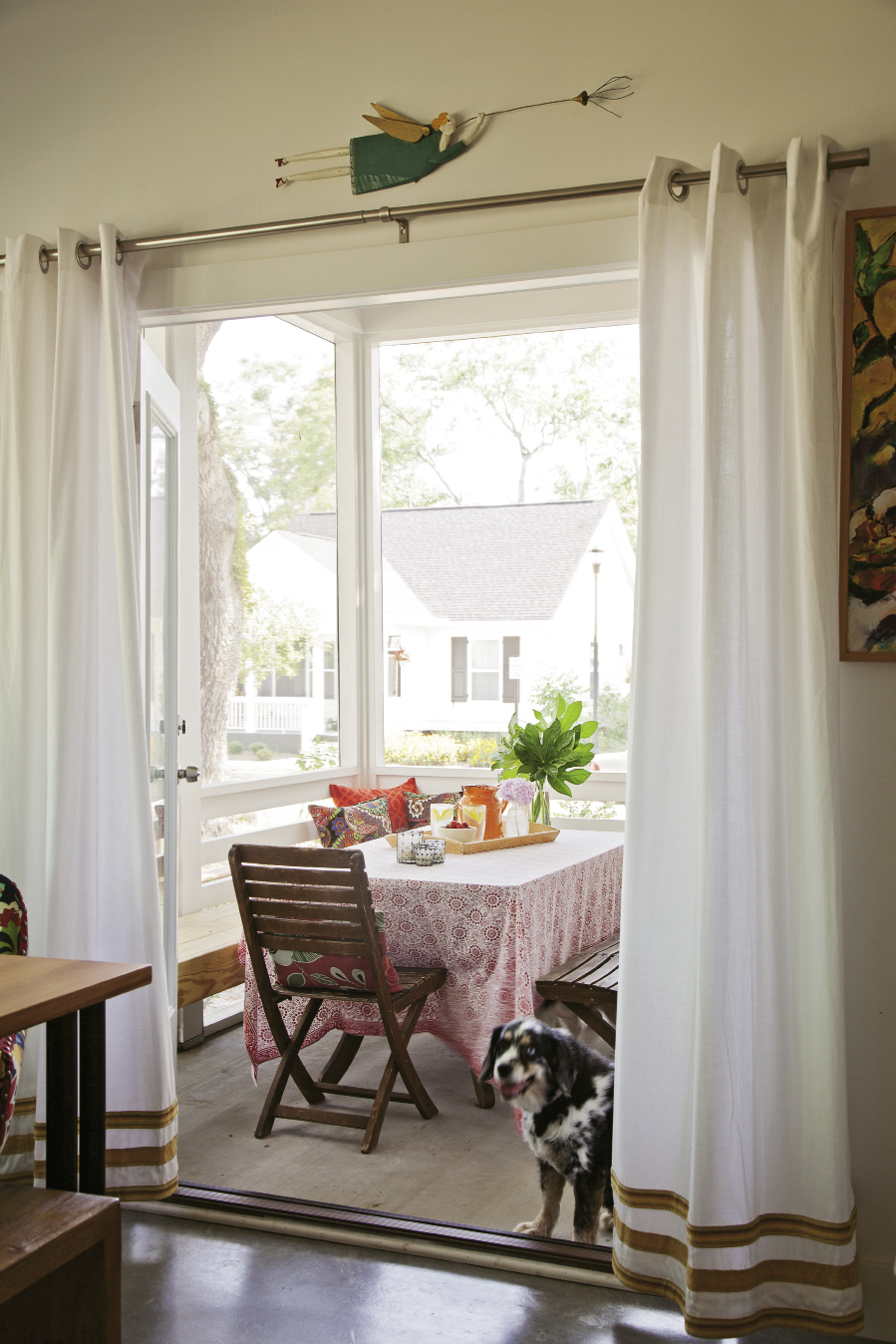 Textiles—some new, others collected over time—brighten the screened-in porch.