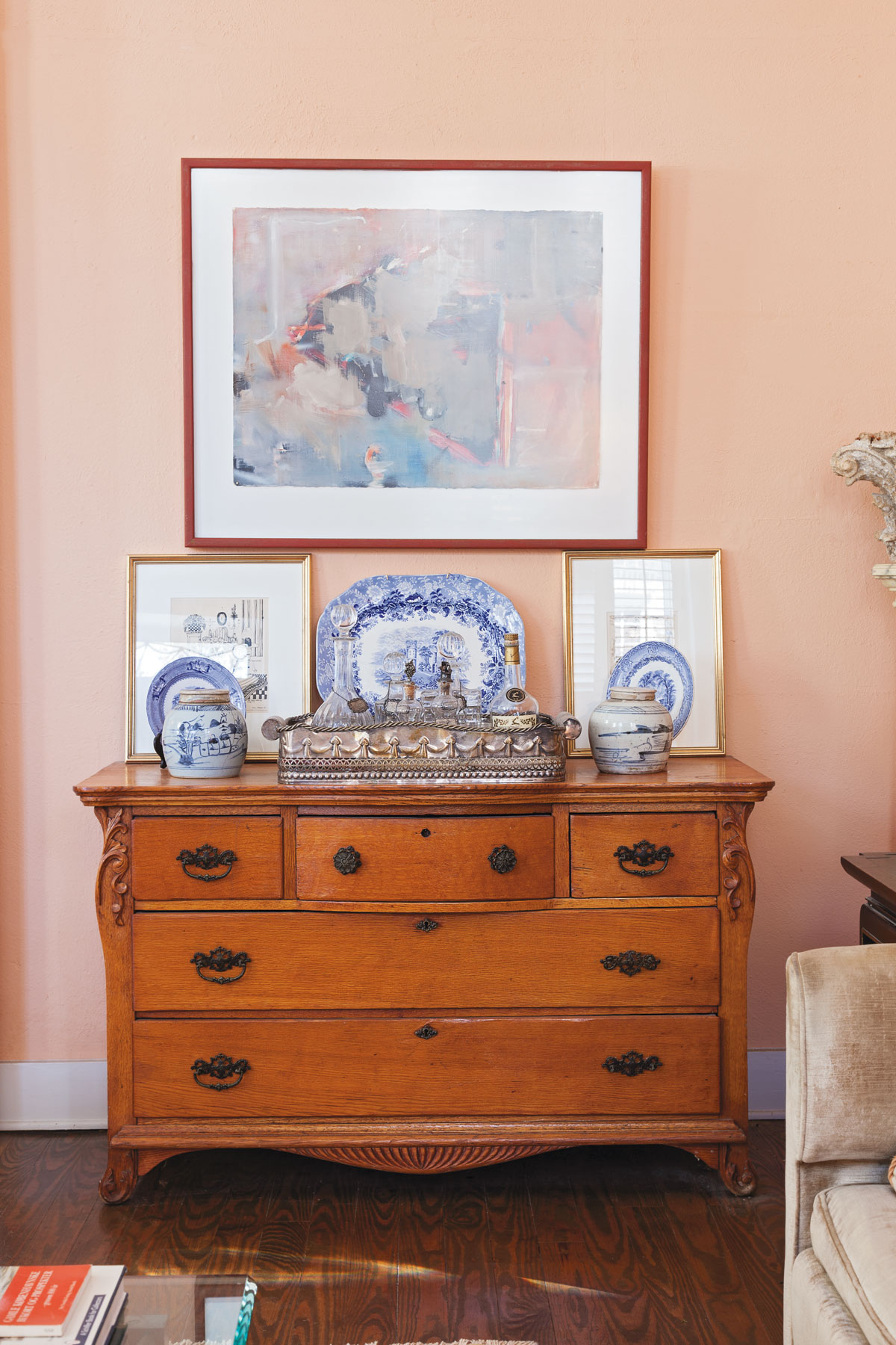 A tableau including blue-and-white pottery, silver, a painting by Eva Carter, and Bigner's own sketches tops an antique bureau.