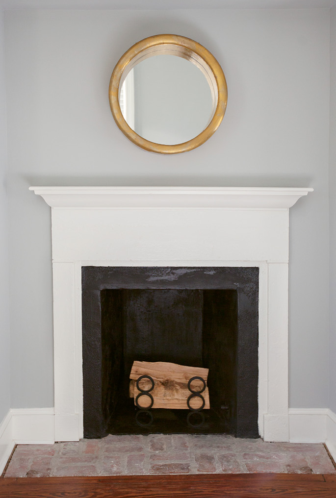 A perfectly simple gilded mirror from Antiques of South Windermere hangs above the fireplace mantel in the guest room.