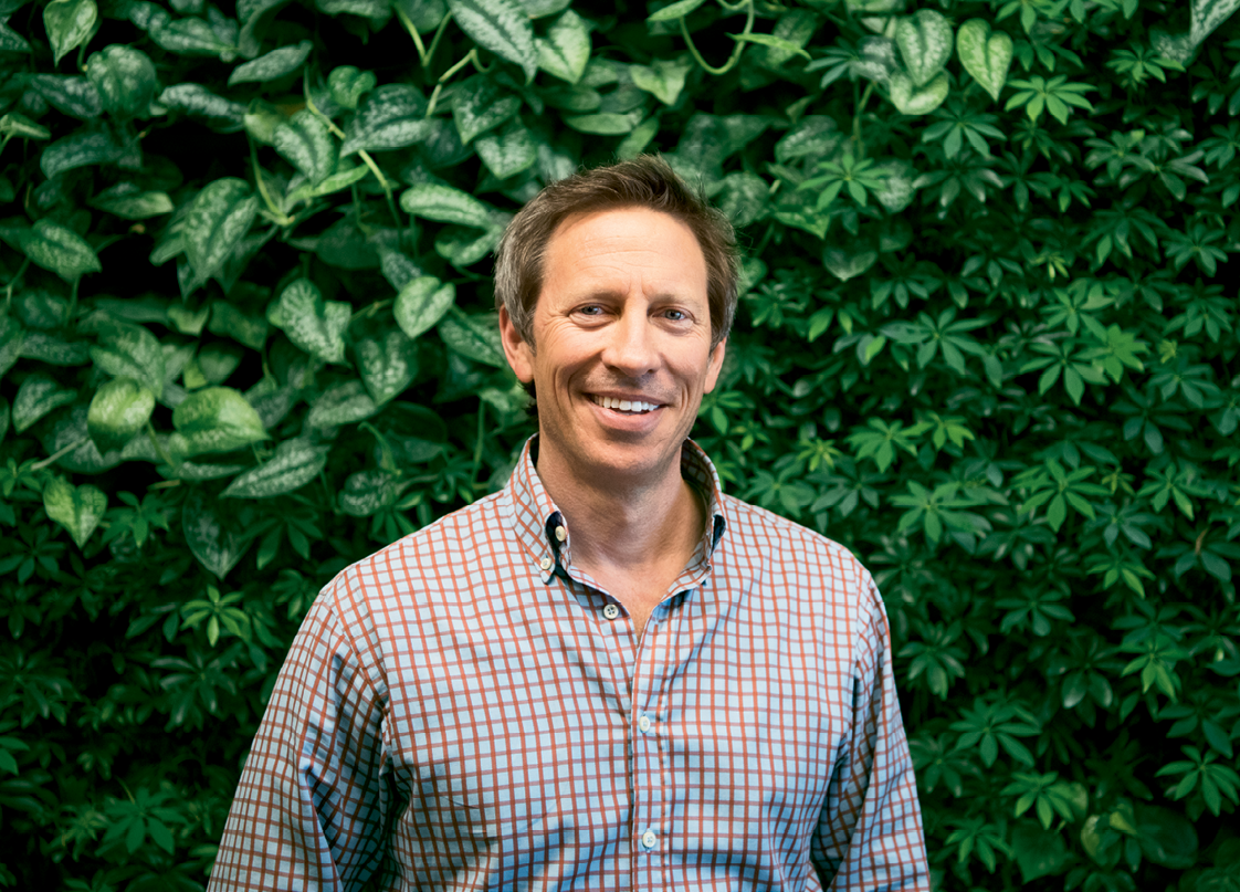 Green Roof Outfitters founder Michael Whitfield in front of a green wall that uses the company's modular system