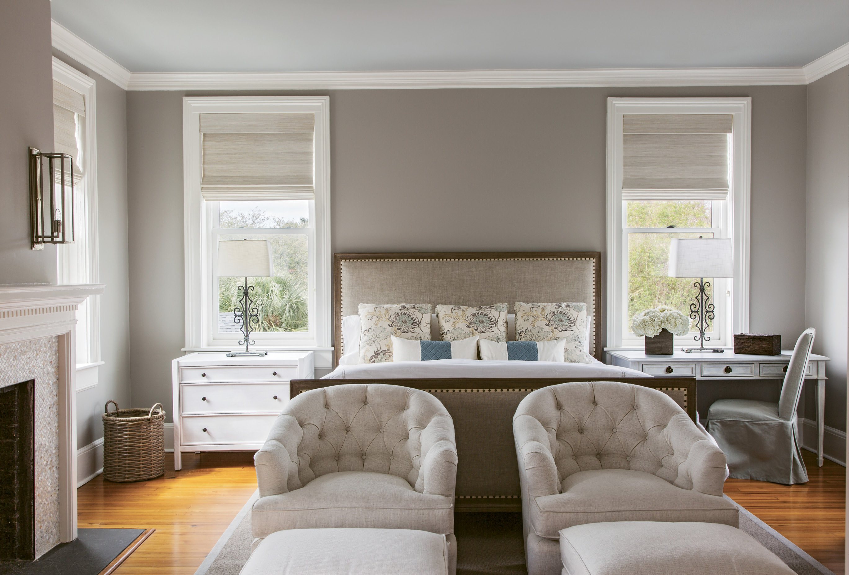 """Neutral Territory: For the master bedroom, Peake worked with a neutral palette conducive to relaxation: Benjamin Moore """"Cumulus Cloud"""" covers the walls, with """"Half Moon Crest"""" on the ceiling. The custom headboard was upholstered in Belgian linen. Natural woven shades provide privacy while still allowing for natural light."""