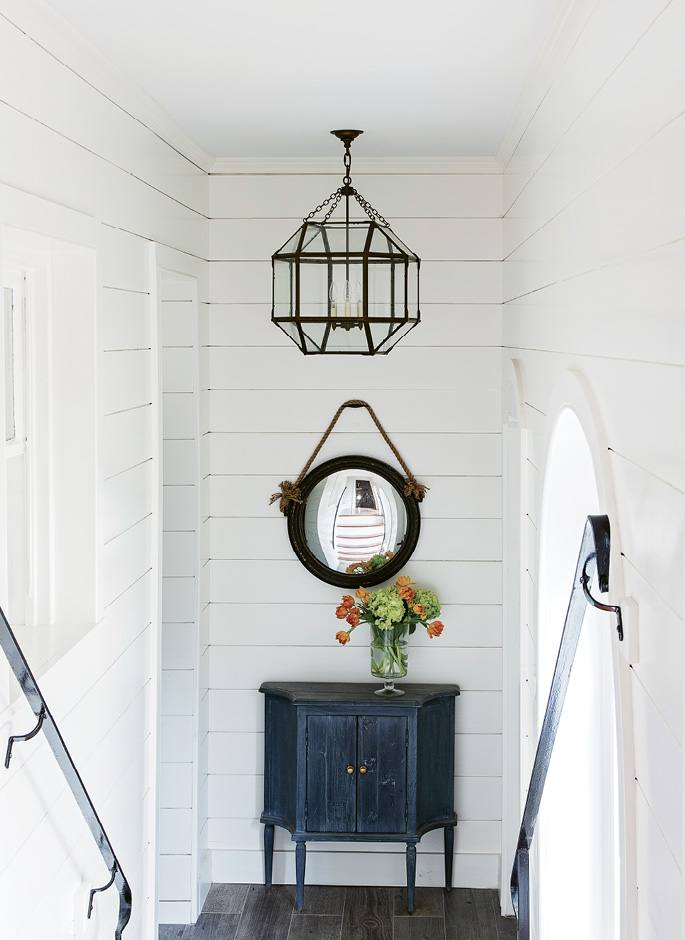 Walk This Way: The steps leading to the second floor are original to the circa-1856 house; a third story was added in the earlier part of the 20th century. Peake painted the stairwell walls white and hung a convex mirror on the first landing to amplify the light.
