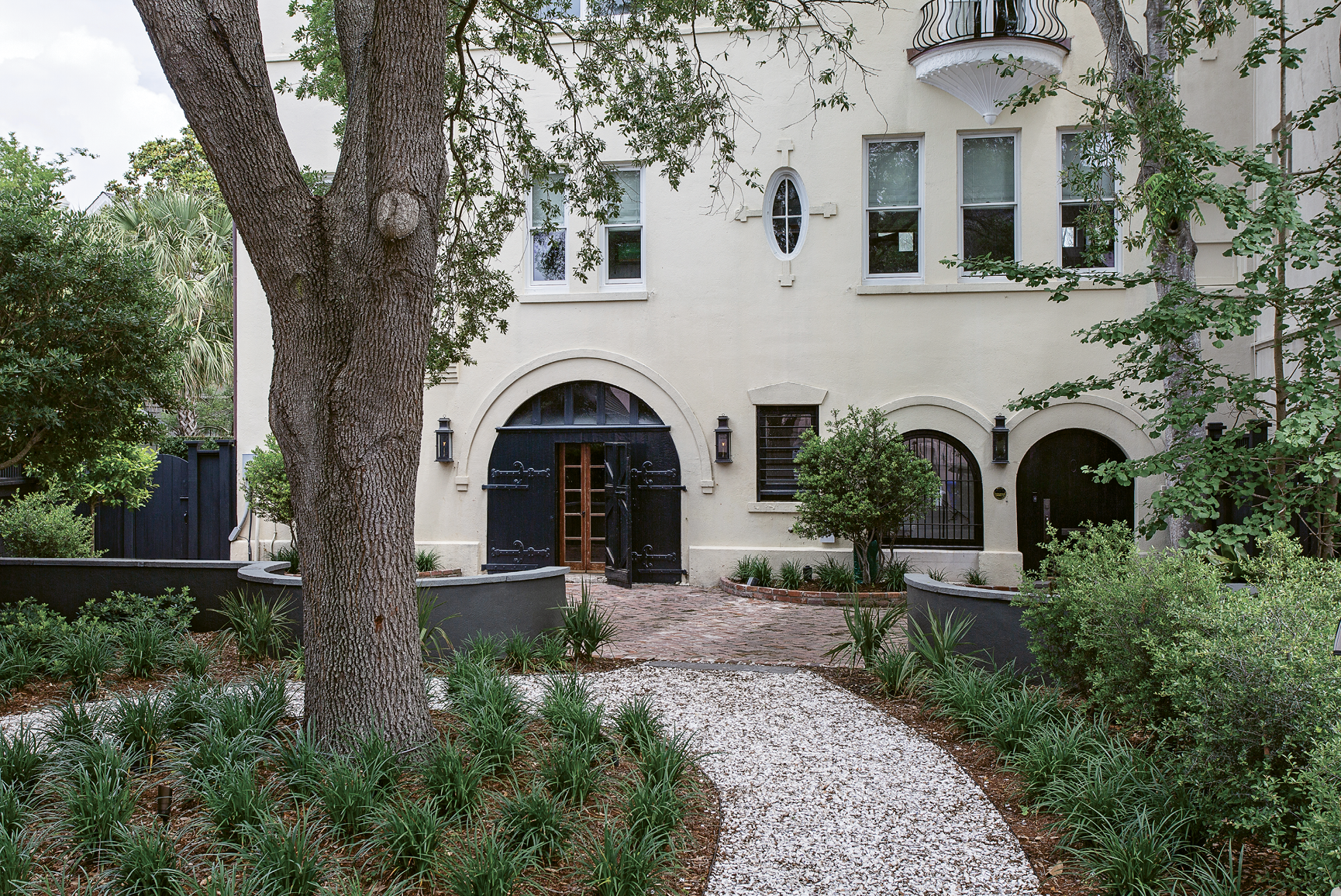"""Go with the Flow: Maryland-based couple Rick and Kristy Schultz """"bought a garage""""—i.e. a three-story carriage house in sight of the Battery—as a second home, enlisting Richard Marks Restorations and Kristin Peake Interiors to transform the formerly drab dependency. Just as renovations were wrapping up, Tropical Storm Irma washed a foot and a half of surge into the ground floor (left), which spurred on storm adaptations. They revised the exterior hardscape with an eye toward drainage and changed up interior materials, furnishings, and electrical wiring to suit."""