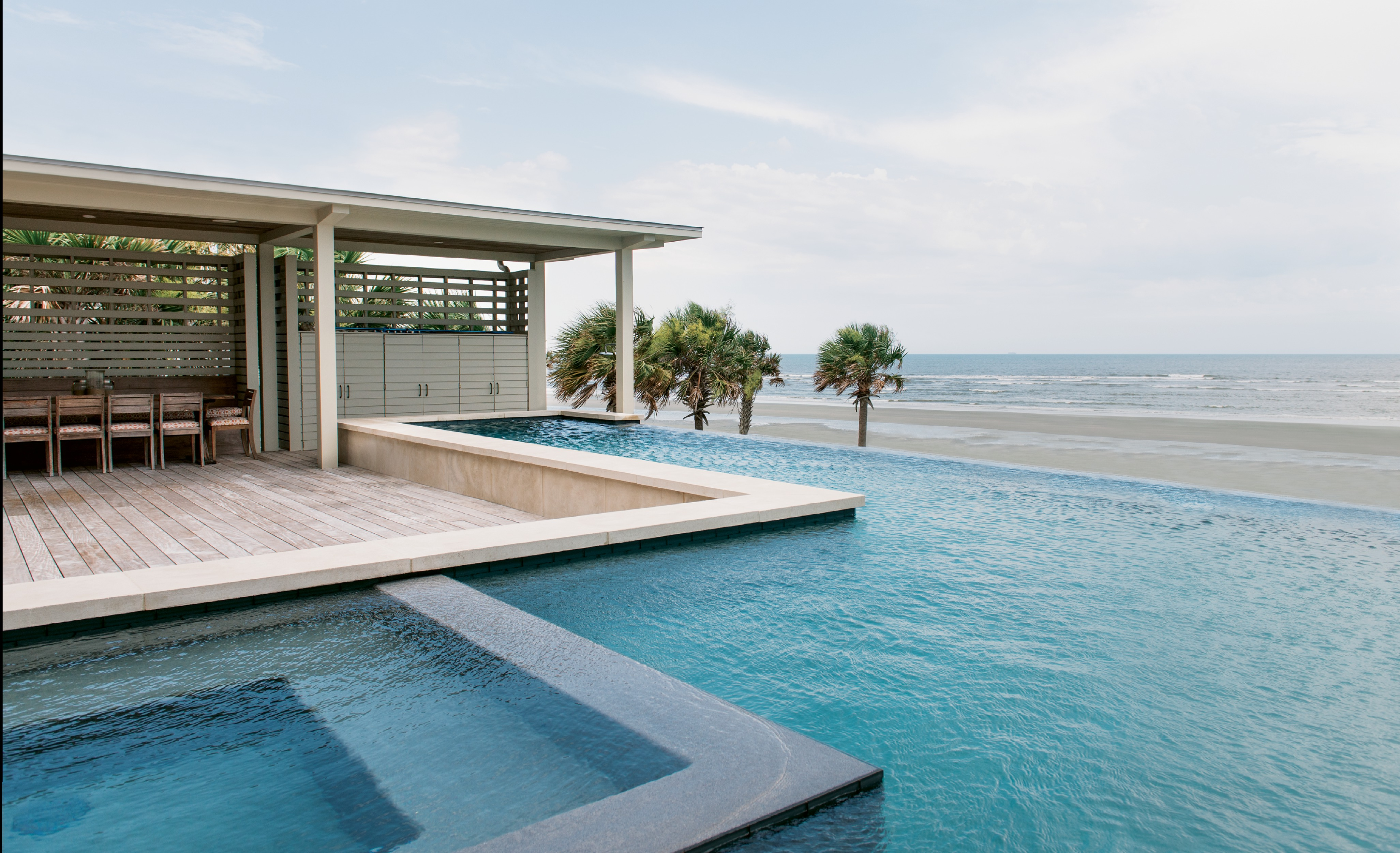 An elevated deck of garapa, a durable Brazilian hardwood, and a zero-edge pool are nested into the house, offering amazing views of the Atlantic.