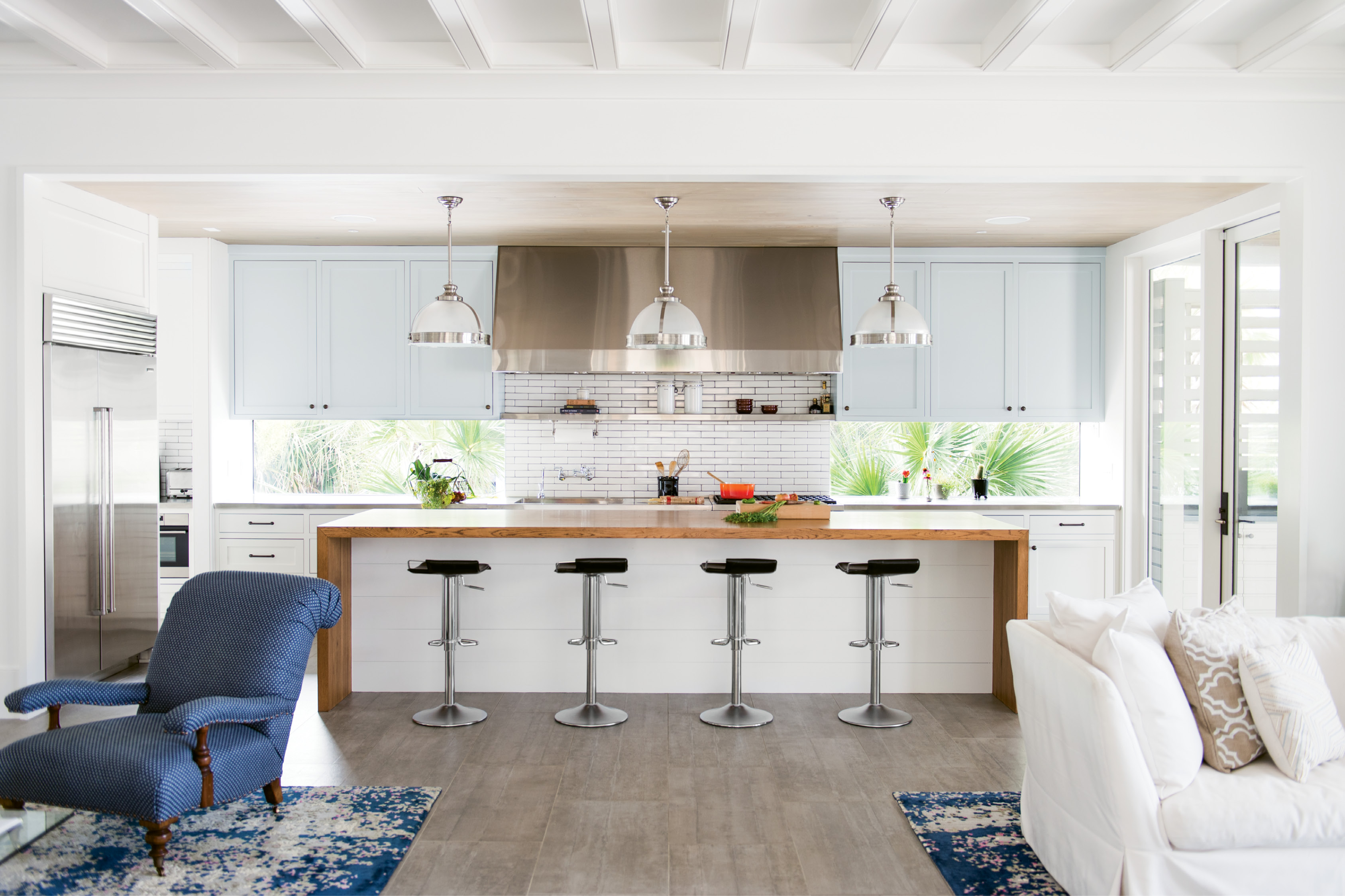 The use of windows over a traditional backsplash helps the home feel more connected to the landscape. Flush cypress ceilings and cement-tile flooring reinforce the modern feel.