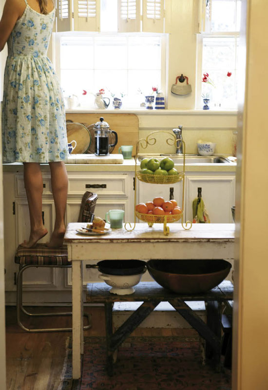 An old sewing table-turned-kitchen-island anchors a petite and sunny cookspace.