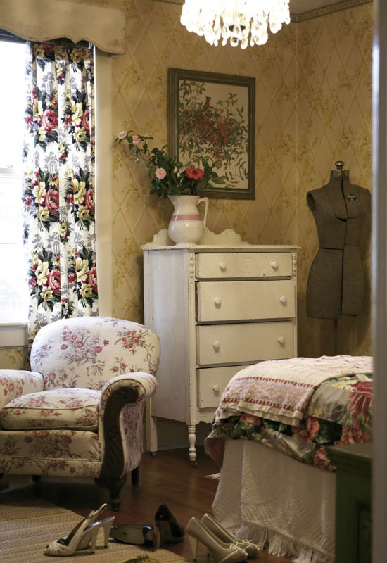 "In the guest room, Hollie paired a ""favorite dresser"" she picked up for $30 with an old dress form and overstuffed armchair. As for the wallpaper, ""The real estate agent said, 'I'm sure you'll tear it down as soon as you get a chance,' and I said, 'No way, that's the best part!'"" recalls Hollie."
