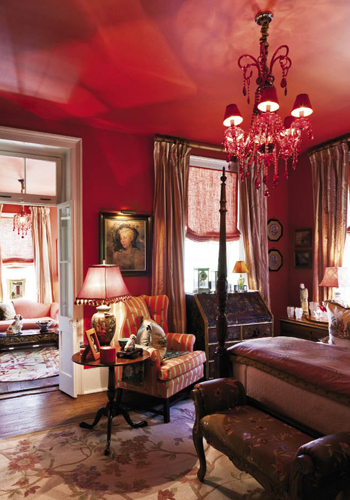 """""""Throughout the house, we wanted color that resonates happiness and daring,"""" says Juan. The second-floor guest suite in the main house is saturated in a fiery shade Juan deems """"pimiento"""" before buoyantly adding, """"and the chandeliers are bordello red."""" Visitors to this """"Scarlet O'Hara Room"""" are afforded their own sitting area and a piazza that presents a sweeping view of the garden."""
