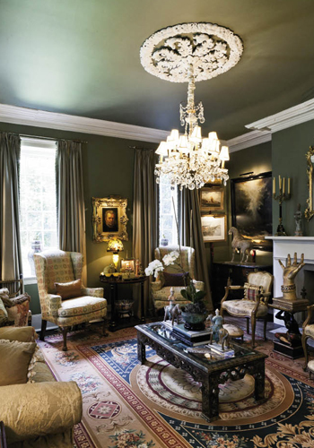 n the formal living room, an elegant French chandelier shines a light on an early-20th-century wood and gilt hand, as if beckoning visitors to the hearth.