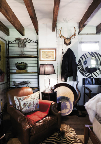 """The """"Safari Room"""" features earth-toned fabrics, rugged furnishings, and African art, as well as game trophies, a zebra-skin rug, and an alligator-skin motorcycle jacket hung on the wall."""