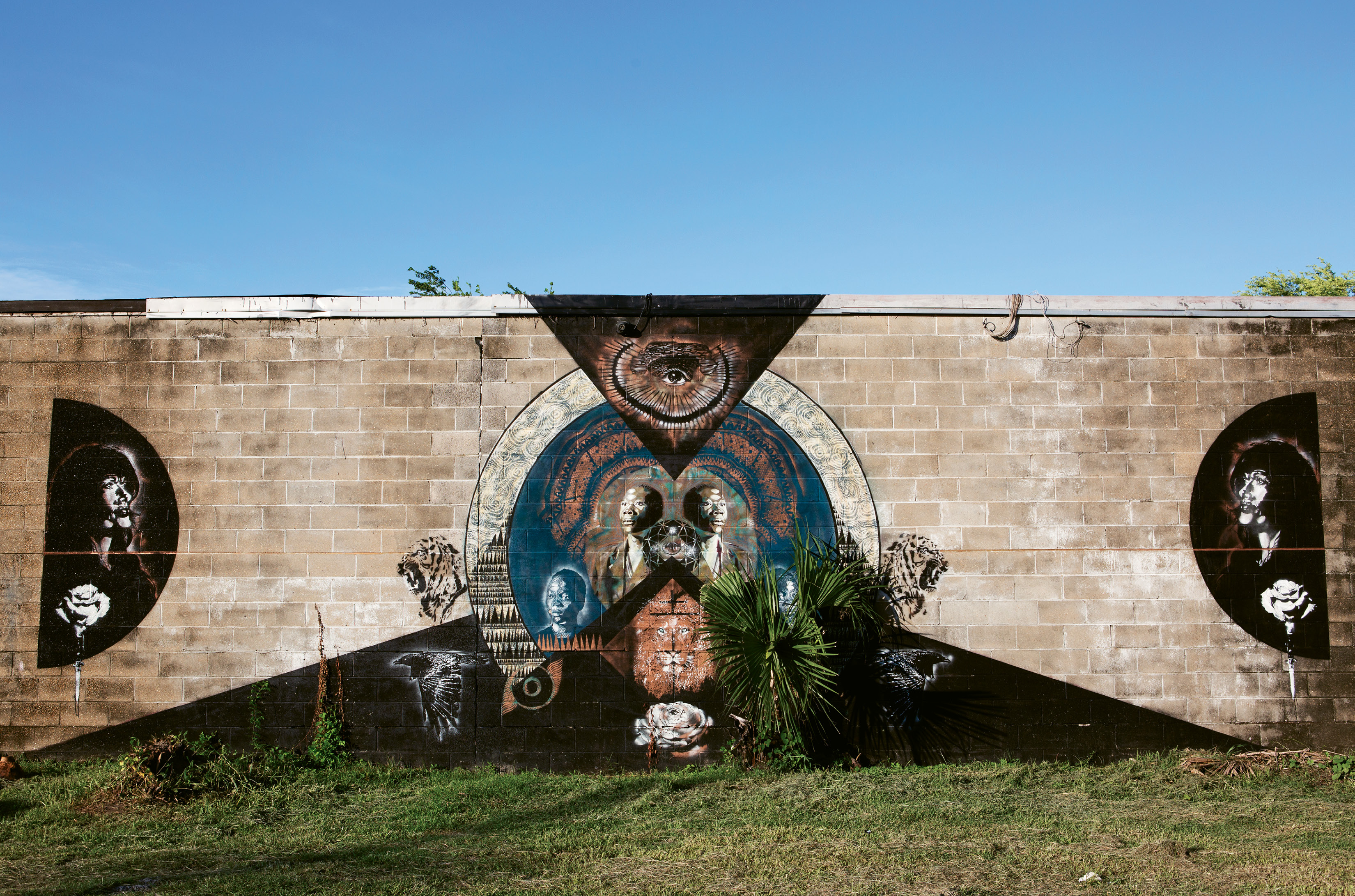 "Living Stone by RC Hagans,  June 2015  (Huger & Hanover streets). Created alongside seven other works for Enough Pie's ""AWAKENING III: SOLSTICE"" community art event, this mural by Alabama-based artist RC Hagans was inspired by a home for boys orphaned by violence and disease in Zambia. he says The central figure is the elder brother and protector: ""His lion's heart and quiet strength make him the perfect watcher for all who walk these streets. If you are weak, may you become strong, if you are strong, protect the weak."""