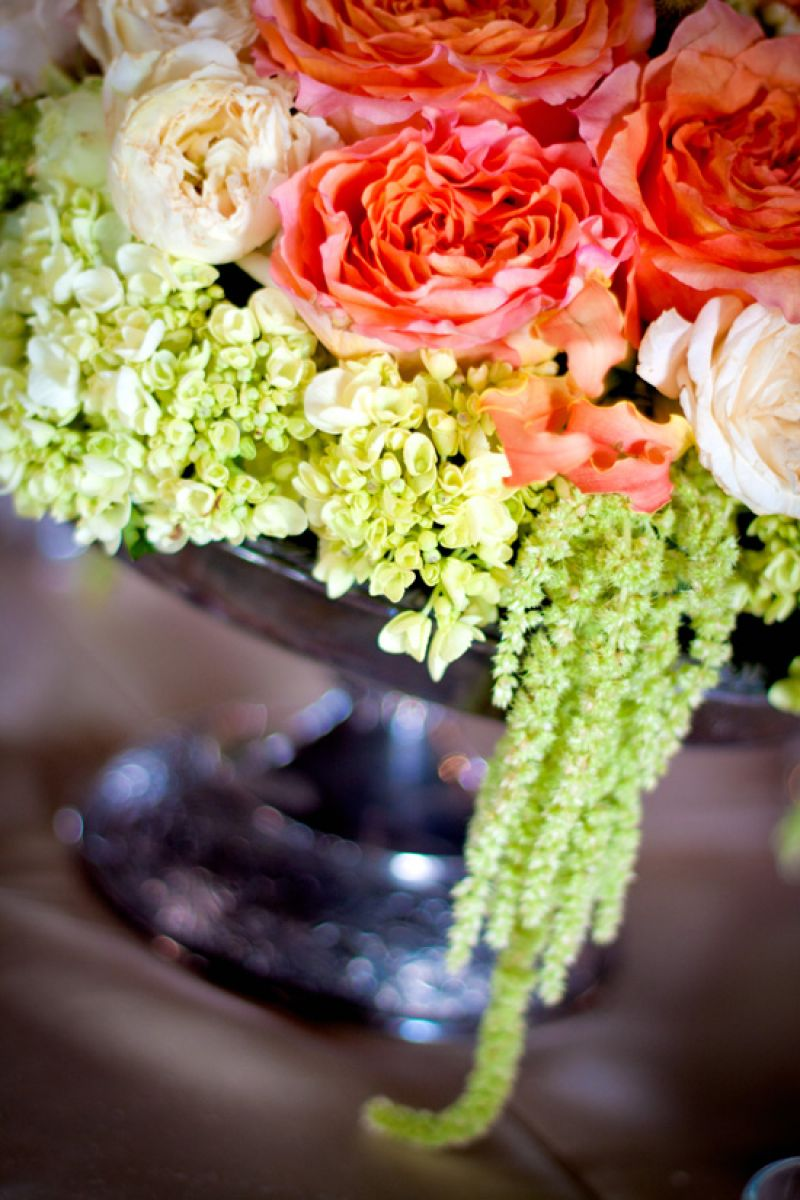 CASCADING CUTIES: Old-fashioned antique roses, green hydrangea, and strands of amaranthus green tails added pale-hued texture to the reception décor; the tarnished silver bowl lent an antique touch to the arrangement.