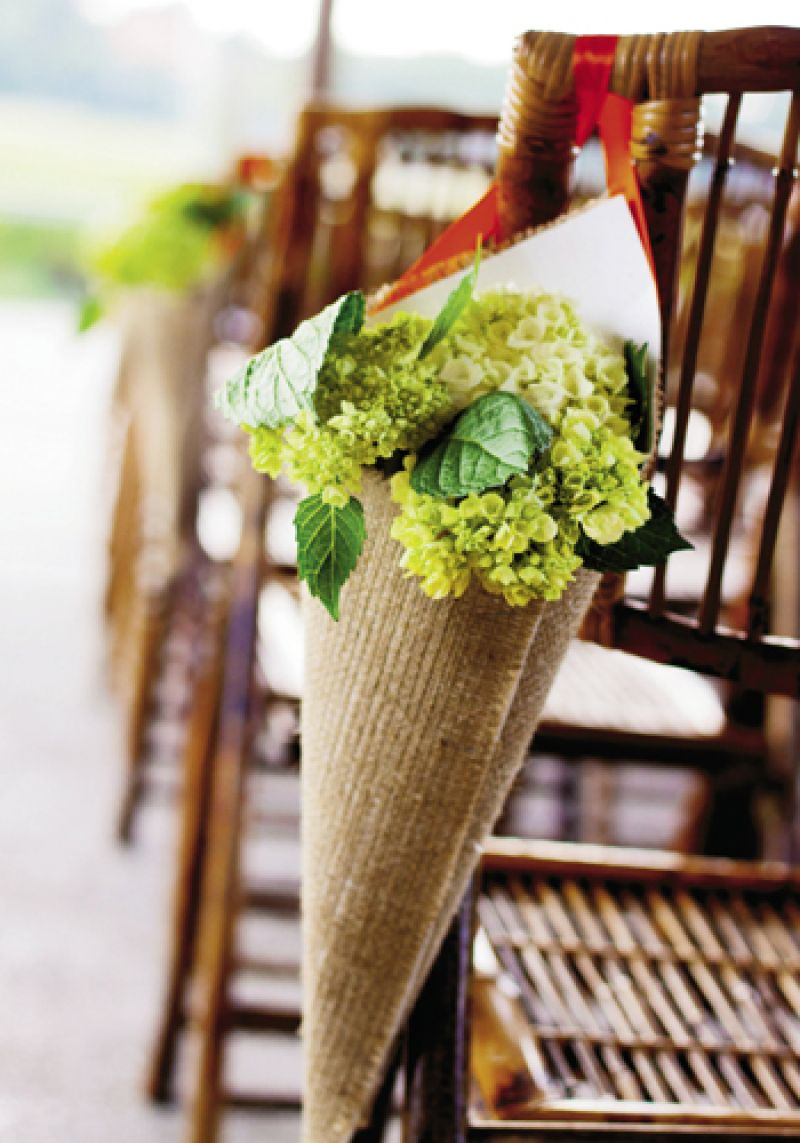NATURAL NOTES: Pale green hydrangeas tucked into taupe woven cones hung along the aisle.