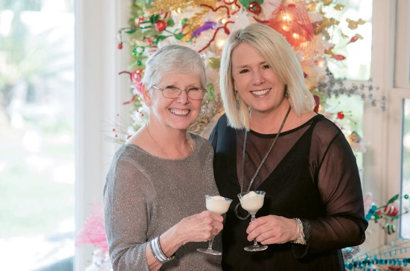 The mother-daughter duo toasts glasses of frothy punch before one of Austin's many Christmas trees.