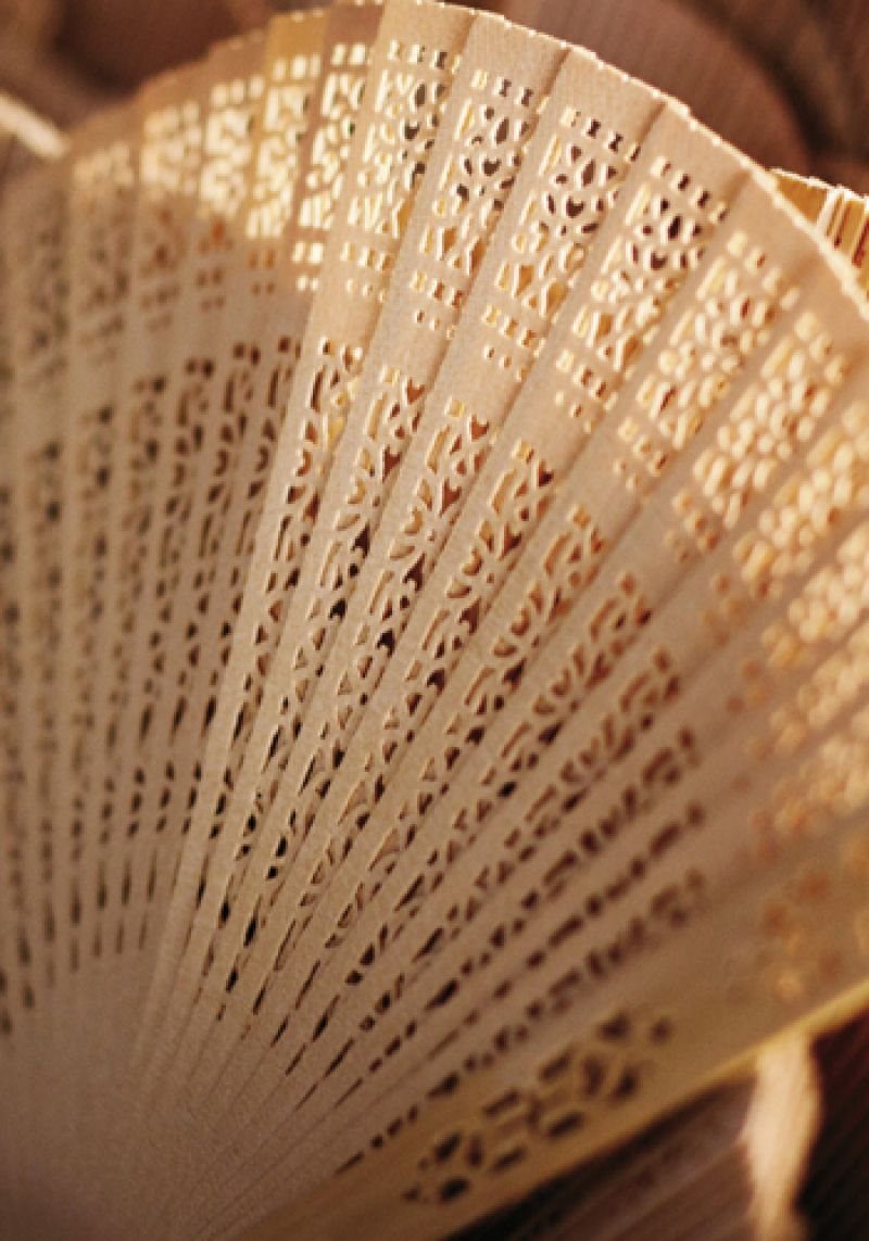 BEAT THE HEAT: Guests fended off warm temps with laser-cut sandalwood folding fans from theknot.com.