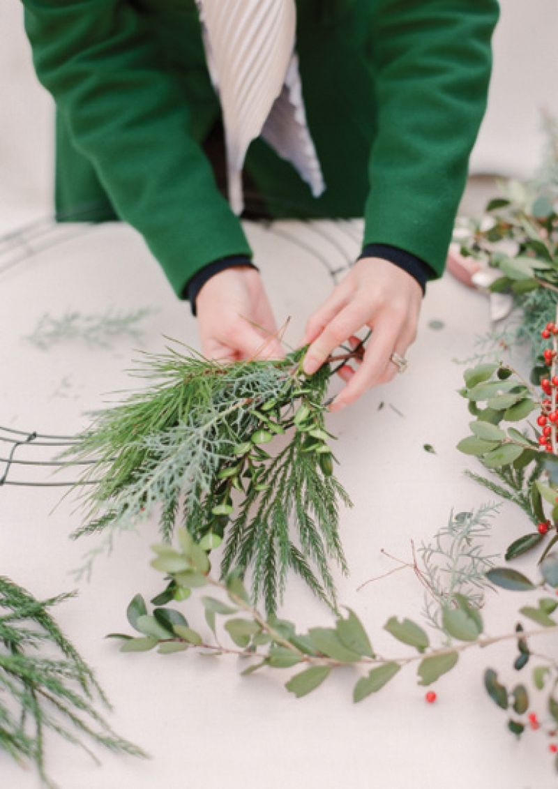 A workshop-goer puts together a spray of evergreen sprigs, including pine, sapphire cedar, and boxwood.