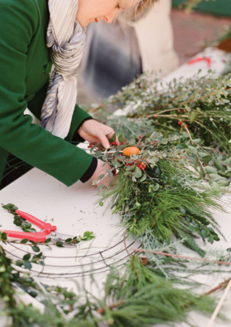 It's best to layer on bundles of accent ingredients—like kumquats and ilex berries—before filling the form with greenery.