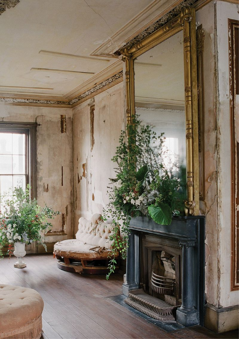 In the Aiken-Rhett's second-floor drawing room, a mantel bursts with Japanese maple, trailing ivy, spray roses, dusty miller, nandina, elephant ears, and more.
