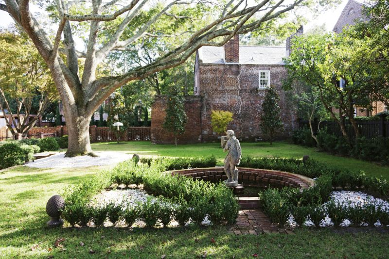 The original owner also purchased the  adjacent lot to house a garden; the courtyard, punctuated by a stately live oak and a French statue, is protected by a conservation easement.