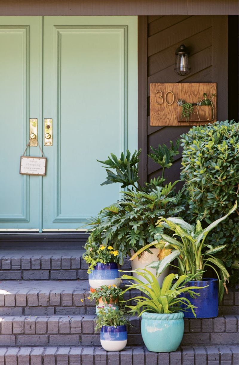 """The brick exterior was transformed with a charcoal shade called """"Ebony Fields;"""" and the front door was given new life with a few coats of """"Tropical Bay,"""" a statement-making turquoise."""