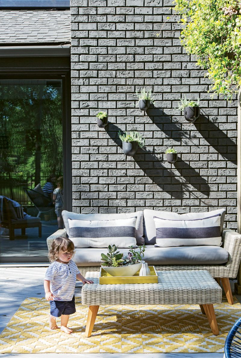 The space is outfitted with World Market furnishings in the same charcoal-and-white color scheme that dominates the interiors; wall-mounted planters from West Elm add a sculptural element to an exterior wall.