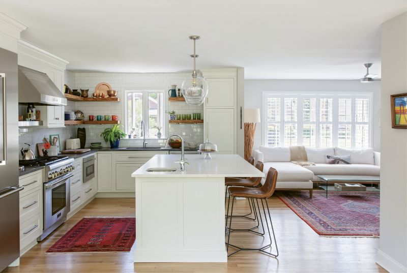 In the kitchen, handsome leather barstools from West Elm—tucked beneath a Calacatta Balena marble island and Pottery Barn globe pendants—offer comfy seating for guests.