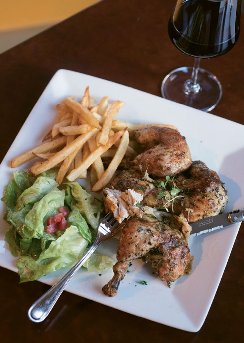 In the casual dining room at Goulette, diners enjoy hearty plates such as signature rotisserie chicken with pommes frites