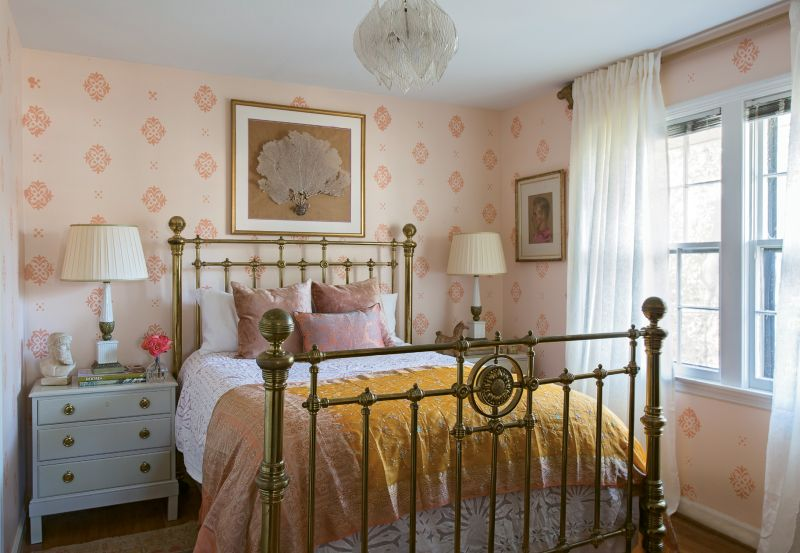 PRETTY IN PINK: In Tinkler's bedroom, a pink-on-pink hand-stenciled motif is more affordable (but no less stunning) than wallpaper. Tall brass bedside lamps and a clear acrylic light fixture help the eight-foot ceilings seem higher.