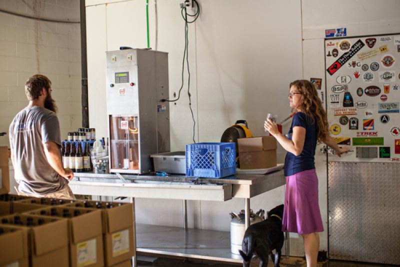 Jaime lets Teach, their dog, in the cooler (he was hot), while David is runs the bottling machine.