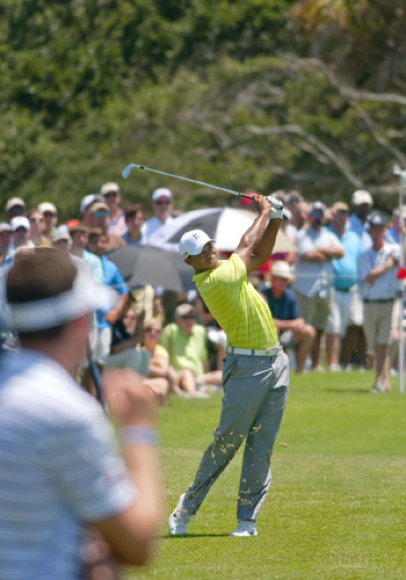 Tiger hits his aproach shot on number 9 while Keegan Bradley watches.
