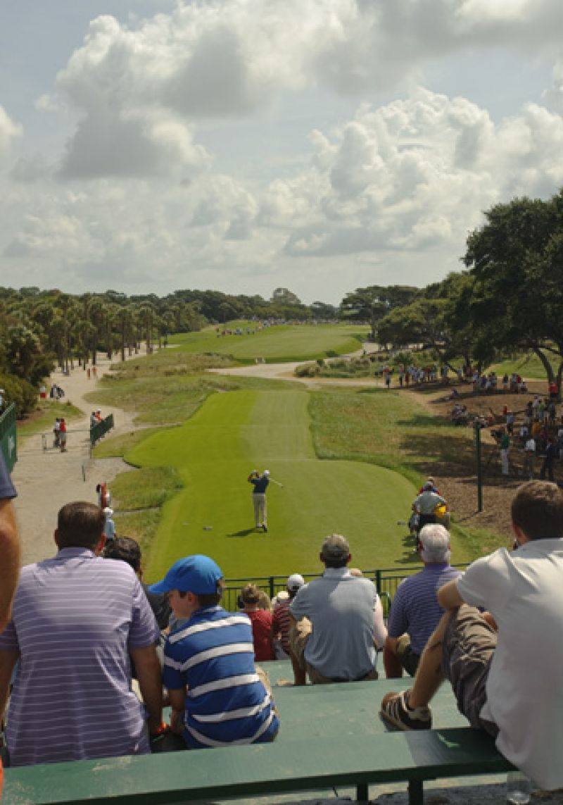 A boy and his father catching the action from the 1st tee.