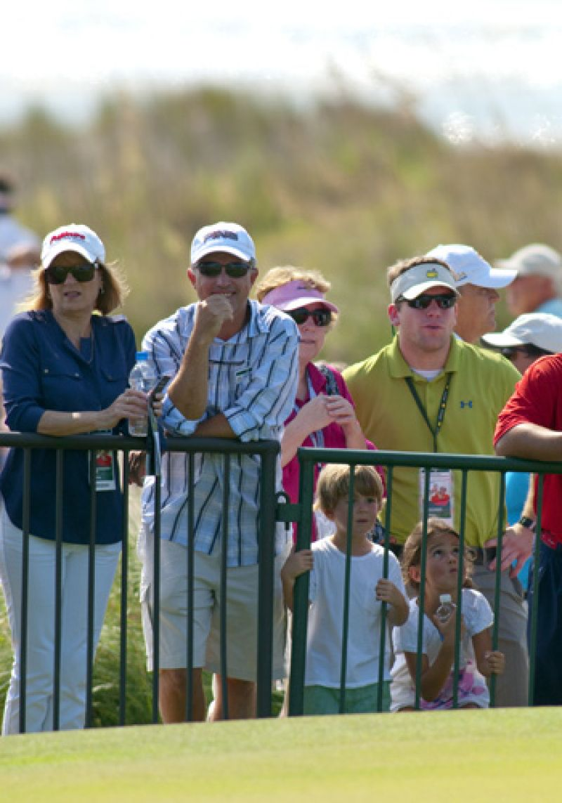 Fans watching Phil Mickelson on the putting green.
