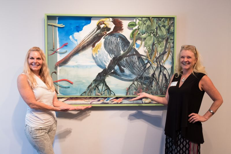 Kaycie Lane and Pam Wimholtz pose in front of the artwork.
