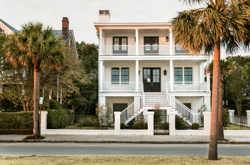 With its double porches, elevated entrance, and graceful symmetry, the home's façade nods to antebellum architecture, but its clean lines and black window mullions are decidedly modern.