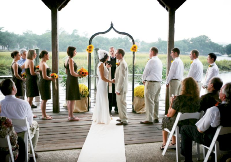 "TWO IN ONE: Holding the ceremony and reception in the same location saved money. As for the view? ""The beautiful marsh was definitely a focal point,"" says Rheney. To add pops of color without competing with the surroundings, they tied two handfuls of sunflowers to the arbor with raffia, and flanked the structure with yellow mums in pots swathed in burlap."