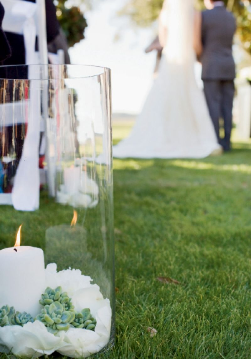 AISLE STYLE: White, vase-ensconced candles flickered from beds of sand topped with flower petals and silver-green succulents.