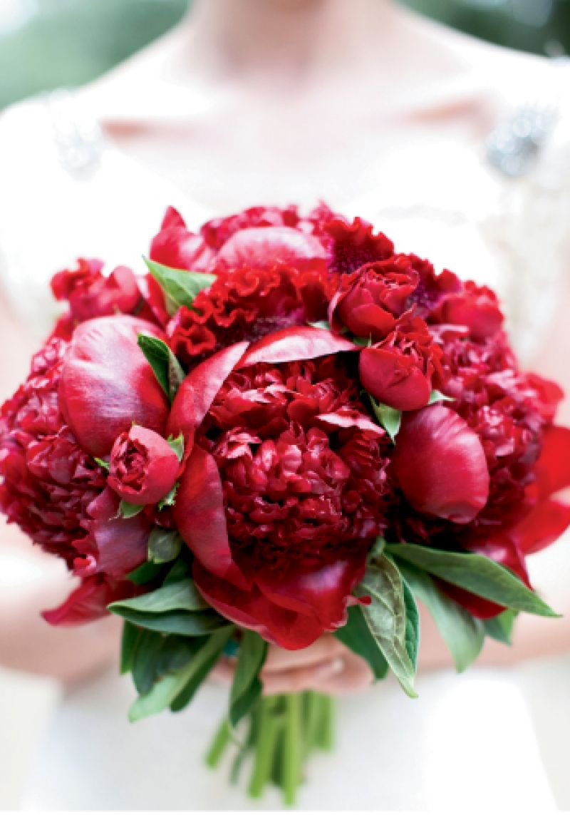 THE BOLD & THE BEAUTIFUL: The intensely red peonies and roses of Ashley's bouquet by Eventa Bella Charleston saturated her walk down the aisle with color.