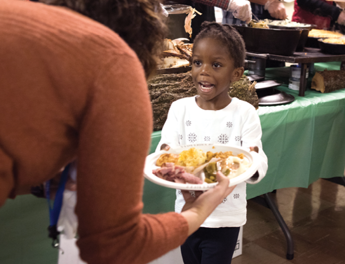 """A young girl accepts a plate loaded up by Feed the Need. Want to lend a hand? Contact Bakst at <a href=""""mailto:mickey.bakst@belmond.com"""">mickey.bakst@belmond.com</a>."""