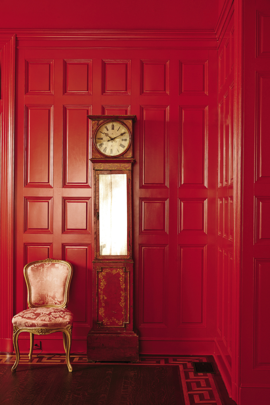 A rich, warm red jazzes up the formal paneling in the dining room.