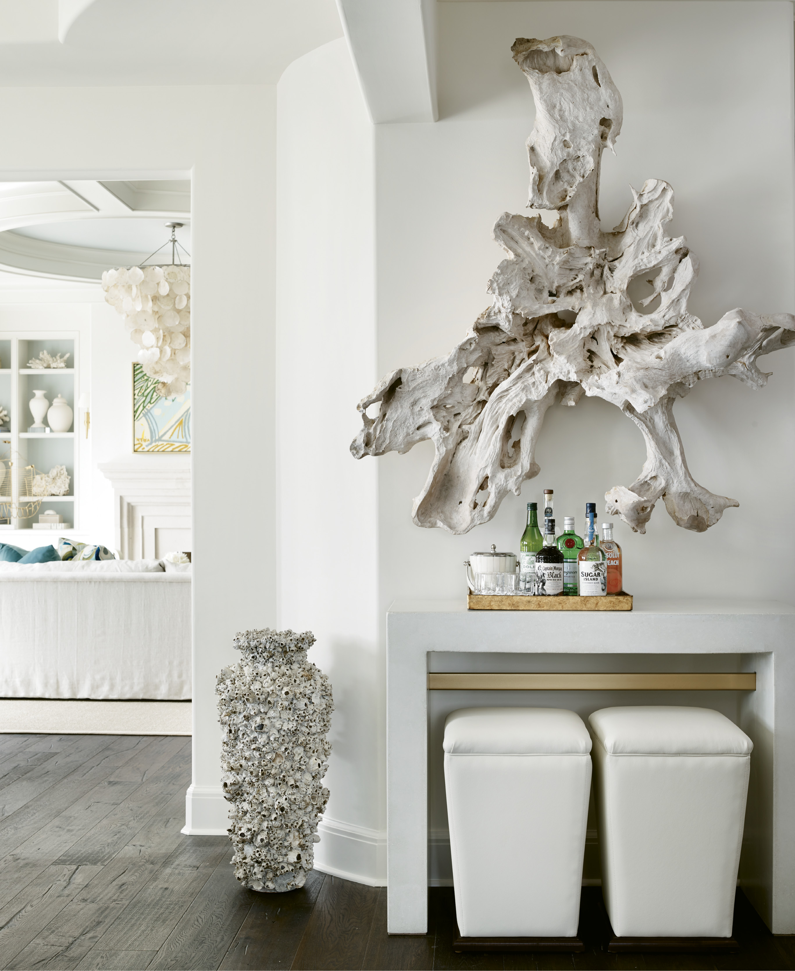 "Though the decor isn't overwhelmingly ""beachy,"" there are nods to the coastal setting, like the piece of driftwood from Bali hung over a Bradley USA concrete console table and a capiz shell chandelier by Oly."