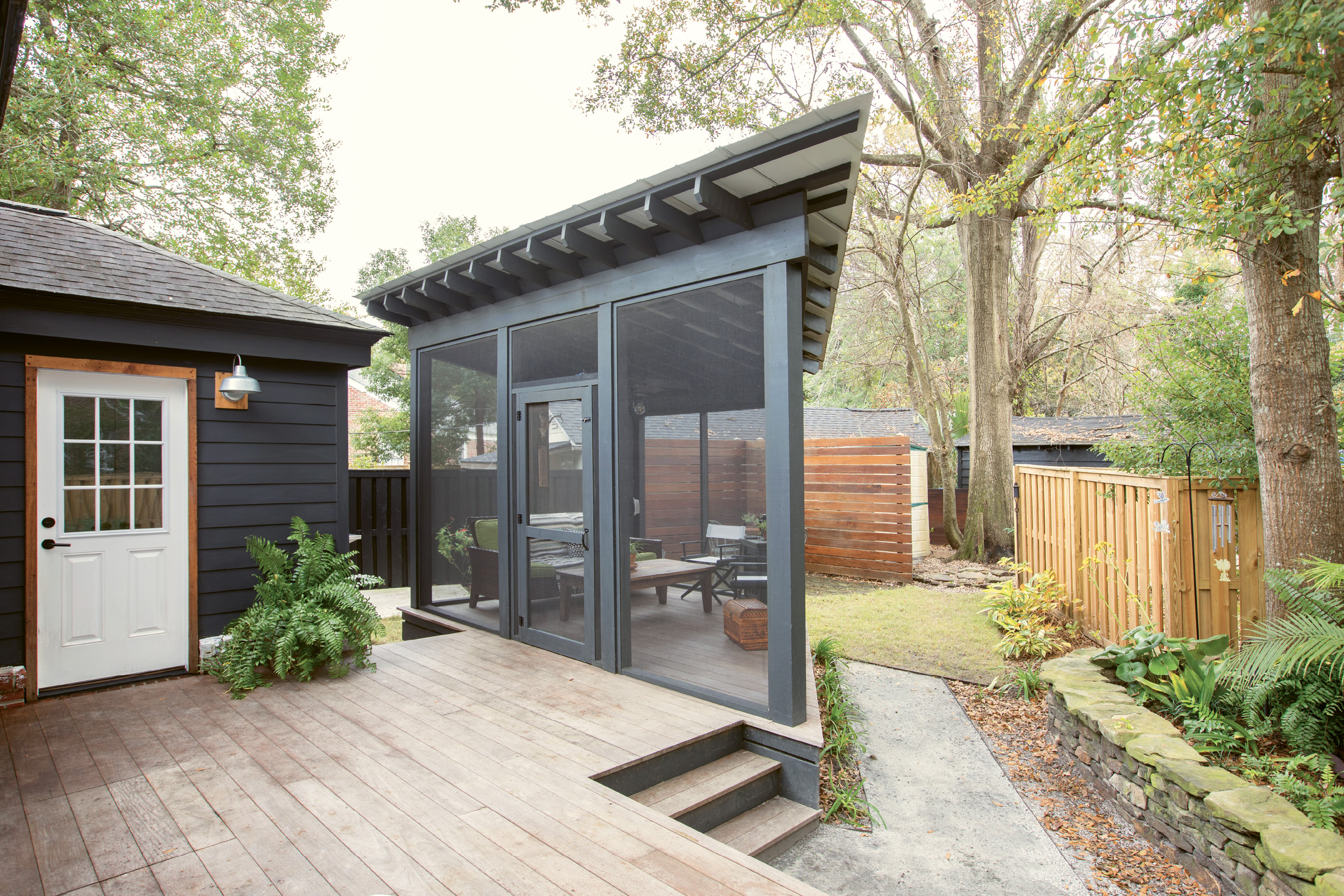 """PRIME PERCH: Just off the back deck, an angular screened-in porch makes the most of the triangular lot; its tin roof adds an industrial touch that feels perfectly in step with the rest of the modern-minded renovation. """"I'm so glad we made the screened-in porch happen: I love being outside, but the no-seeums drive me nuts,"""" Jacques says. """"There's nothing better than sitting on the couch outside, listening to the wind blow, birds sing, and children playing in the neighborhood."""""""