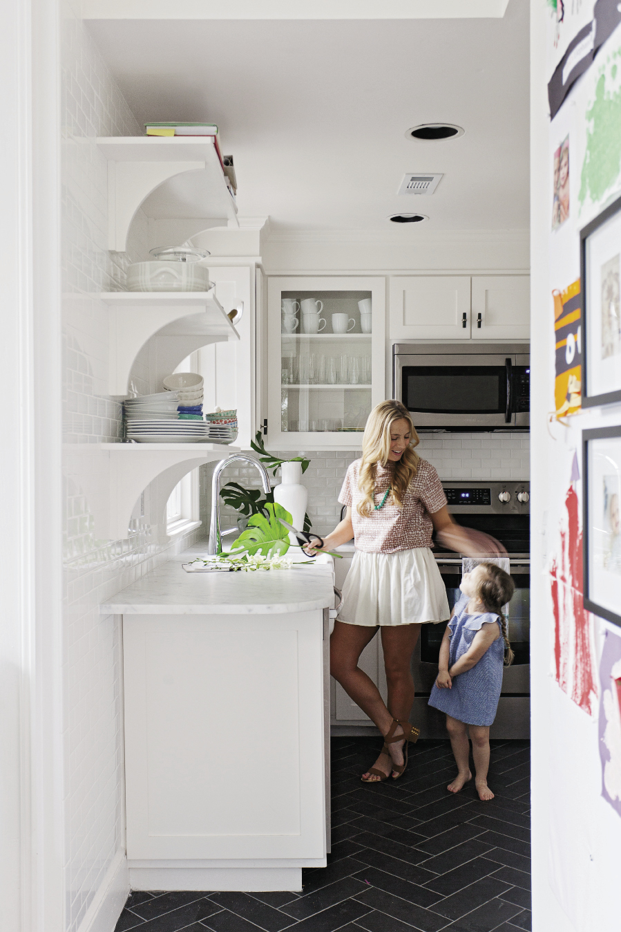 Small Serving The tiny kitchen lives large with new marble counters, a classic coat of white, and glass-front cabinets. Floor tiles in a herringbone pattern add fun contrast.