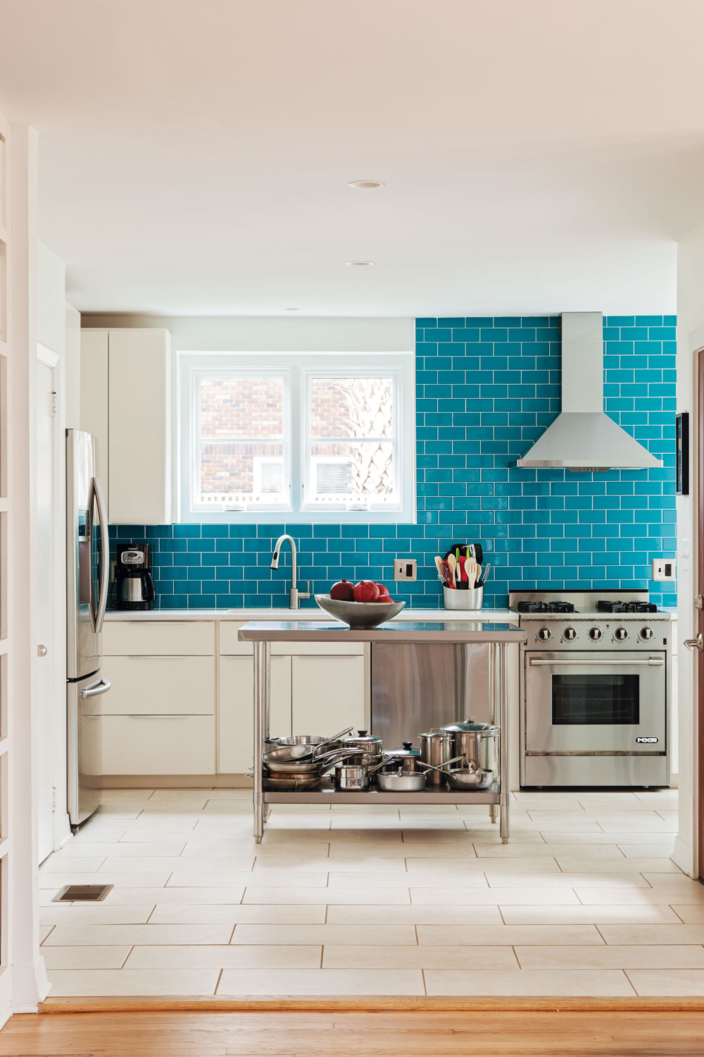 """""""COAT"""" d'AZUR: A wall of bright blue subway tile delivers a splash of color to the modernized kitchen, with new stainless steel appliances, custom cabinets, and Daltile countertops."""