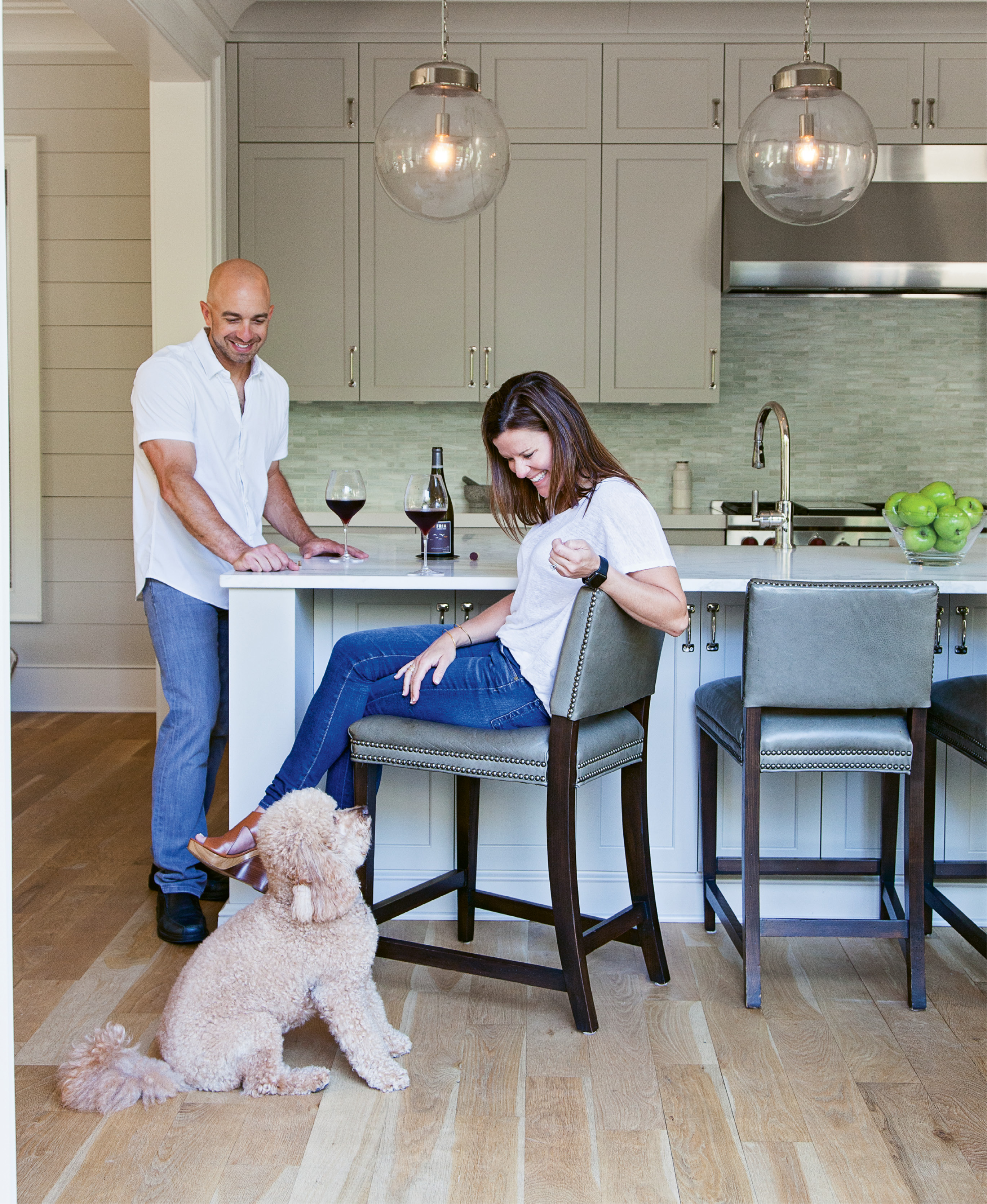 """His passion for all things food and wine were the driving force behind the kitchen design, including his insistence on an """"island that's almost too big,"""" he says. Rusty, their mini Goldendoodle, blends in (adorably) with the unfinished white oak floors."""