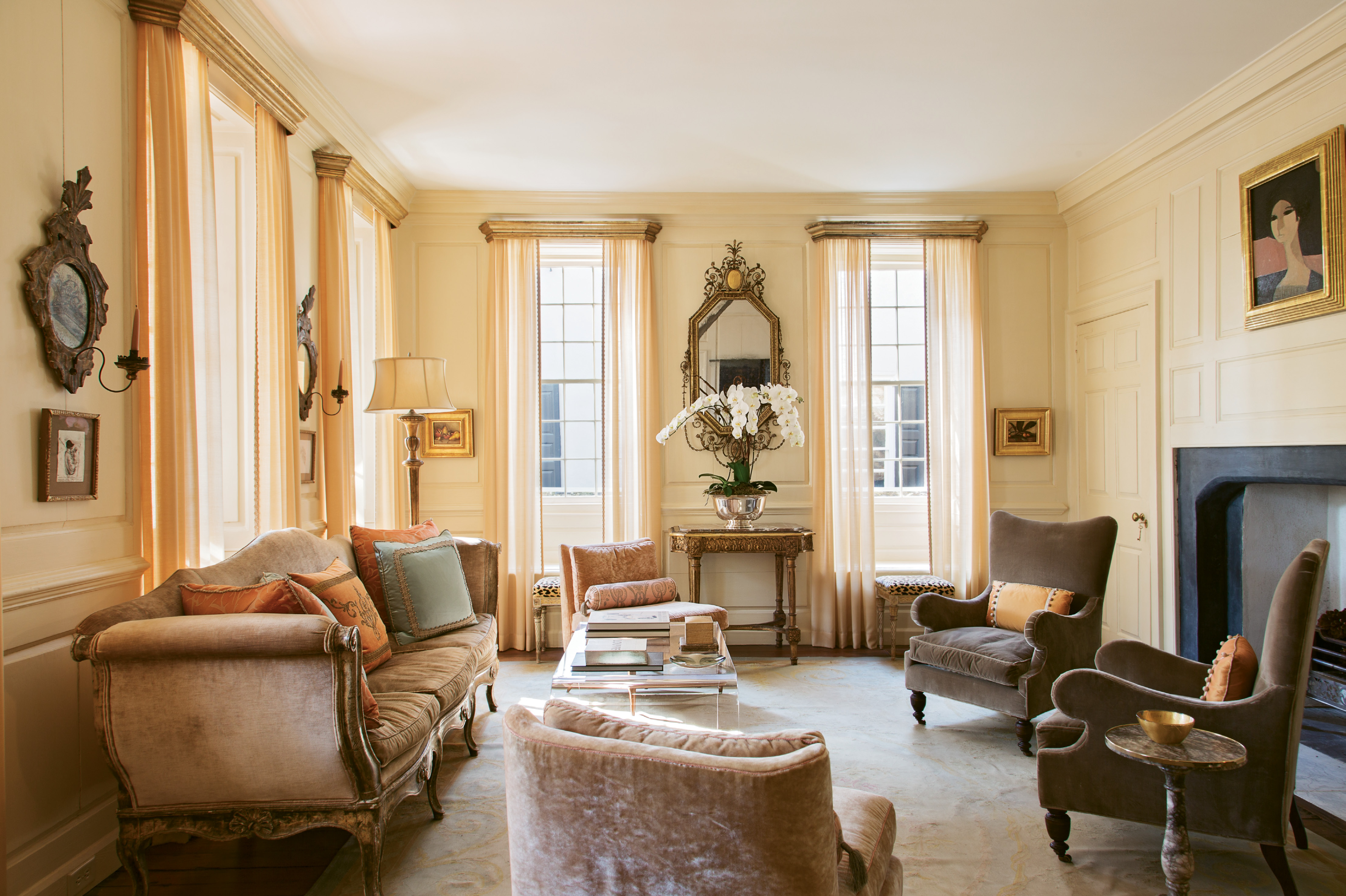 """A 1968 portrait by French painter André Minaux sets the tone for the first-floor drawing room. """"She has that little bit of pink,"""" says Ann. """"We put her right over the classical Georgian fireplace and suddenly the room got very feminine."""" Sketches by Ben Long and two still lifes by Jill Hooper round out the room's luxe vibe."""